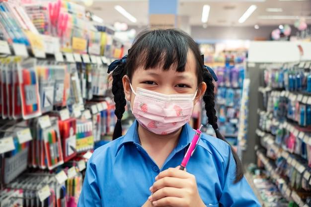 Uniform student girl tragen gesichtsmaske und kauf von schulmaterial im schreibwarengeschäft. zurück zum schulkonzept