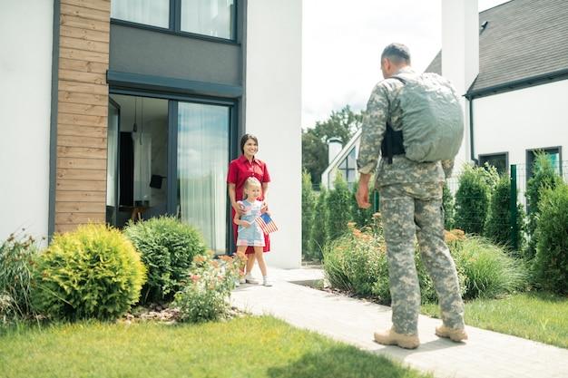 Uniform und rucksack. militärmann in uniform und rucksack, der zu frau und tochter nach hause kommt