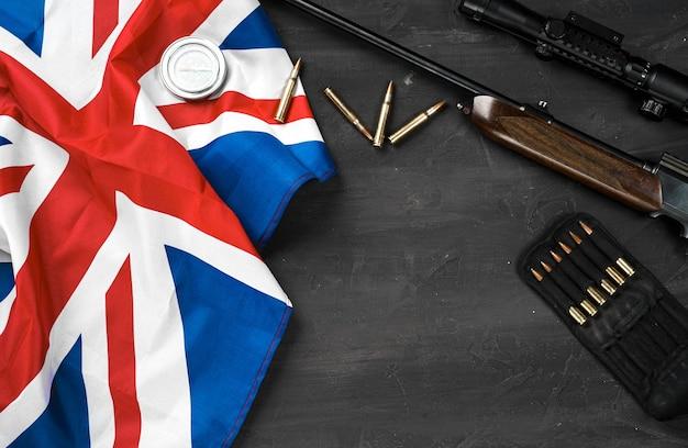 Union jack-flagge mit gewehr und patronen auf schwarzem hintergrund