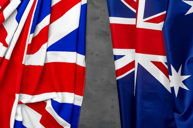 Union jack flagge und flagge von australien auf grauem hölzernem hintergrund