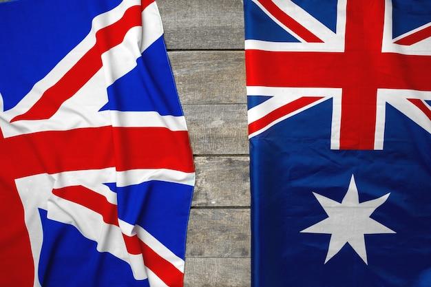 Union jack flagge und flagge von australien auf grauer hölzerner hintergrundoberansicht