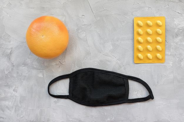 Unisex wiederverwendbare mundmasken aus schwarzer baumwolle mit grapefruit und pillen in blisterpackung