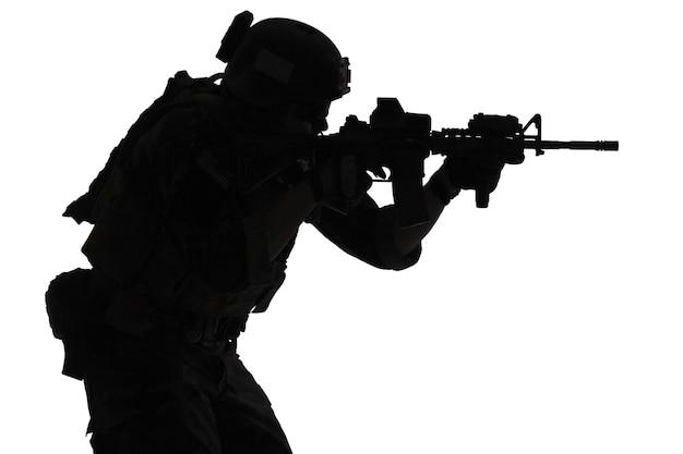 United states marine corps special operations command marsoc raider mit waffe mit dem ziel einer waffe. silhouette von marine special operator weißer hintergrund