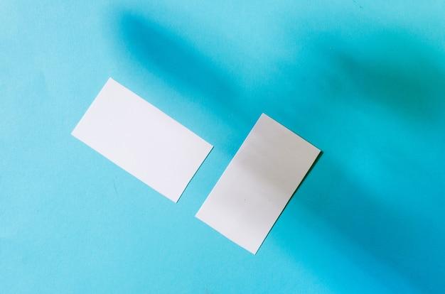Universelle leere vorlage einer modellvorlage mit zwei visitenkarten mit schatten auf blauem papierhintergrund. platzieren sie ihr design.