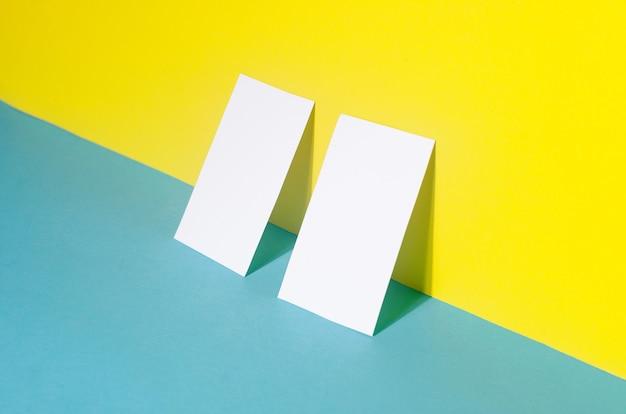 Universelle leere vorlage einer modellvorlage mit zwei visitenkarten mit schatten auf blauem und gelbem papierhintergrund. platzieren sie ihr design.
