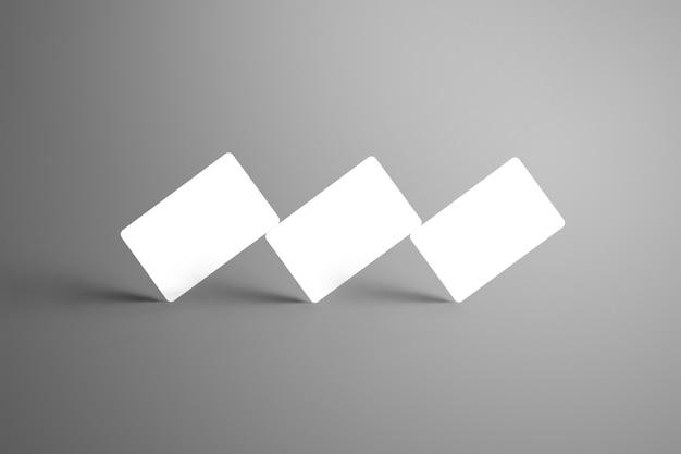 Universelle weiße geschenkkarten mit drei banken, die an einer ecke stehen, isoliert auf einer grauen oberfläche. bereit, in ihrem design verwendet zu werden.