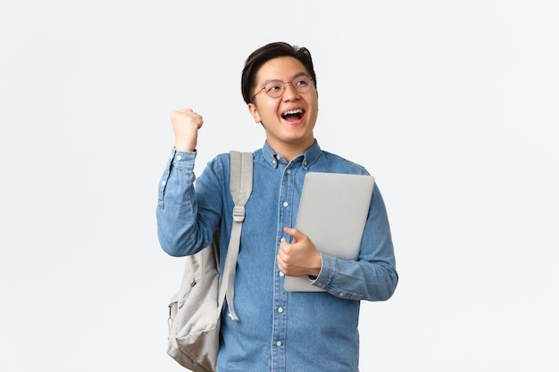 Universität, auslandsstudium und lifestyle-konzept. fröhlicher, jubelnder asiatischer männlicher student mit triumphierenden hosenträgern, bestandene prüfungen, abschluss des letzten semesters, faustpumpe und schreien mit zufriedenheit ja, laptop halten.