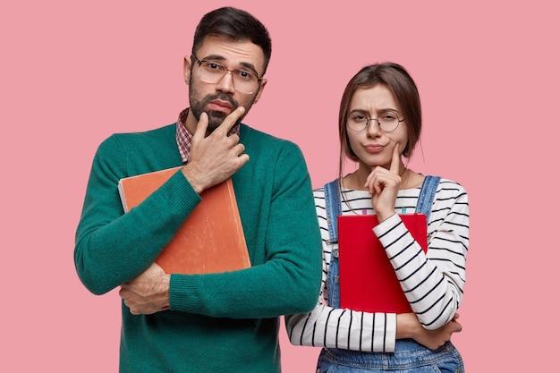 Universitätsfreunde haben nachdenkliche ausdrücke, tragen altes buch und notizblock, denken über die richtige entscheidung nach