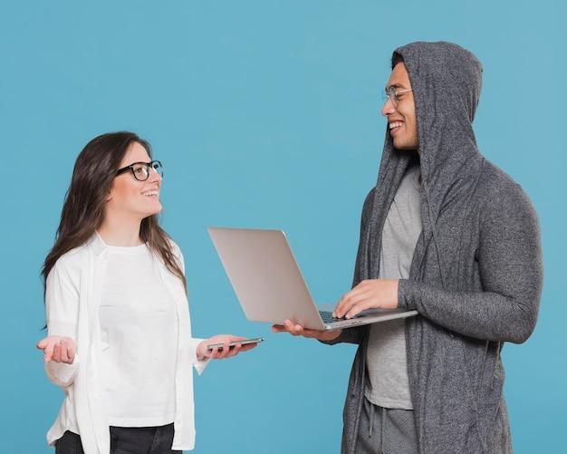 Universitätsklassenkameraden, die sprechen und mann, der laptop hält