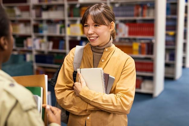 Universitätskollegen sprechen in der bibliothek