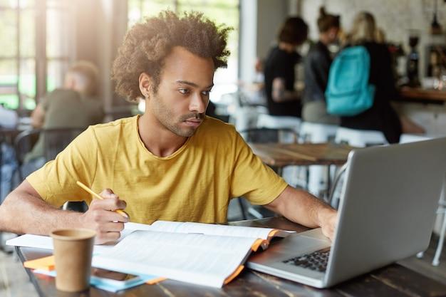 Universitätsstudent mit dunkler hautfarbe und afrikanischer frisur, der im café sitzt und mit büchern und notizbuch arbeitet, während er sich auf die prüfung vorbereitet, die notwendigen informationen im internet findet, die ernstes aussehen haben