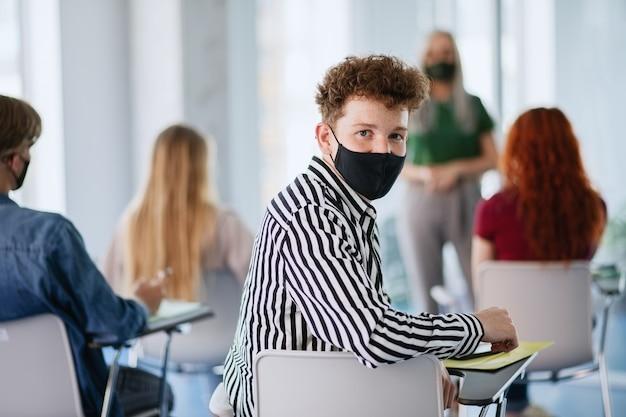 Universitätsstudenten mit lehrer im klassenzimmer drinnen, coronavirus und zurück zum normalen konzept.