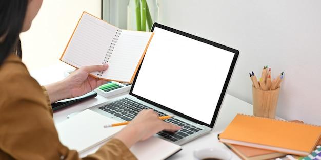 Universitätsstudentin, die ihre hausaufgaben macht, indem sie weißen computer-laptop des leeren bildschirms verwendet, während sie am weißen schreibtisch über bequemem schlafzimmer sitzt