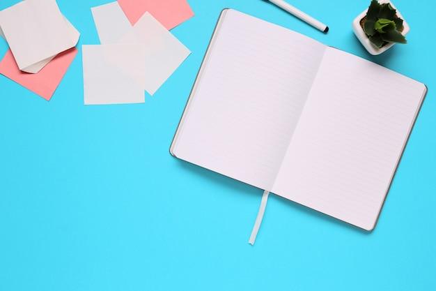 Unkosten des bürotischs mit notizblock, notizbuch und uhr und filzstift. kopieren sie platz