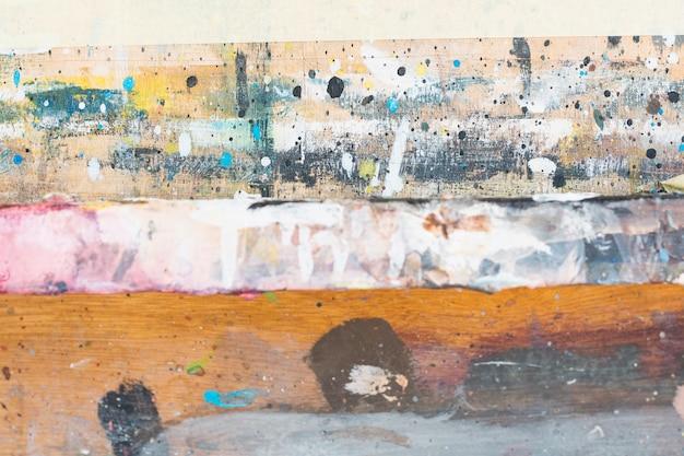 Unordentlich gemalt gemasert auf hölzernem hintergrund des schmutzes