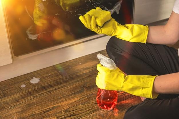 Unordentliche hausarbeit und küchenreinigung, müde weibliche frau im gummihandschuh und sprühflasche in der hand
