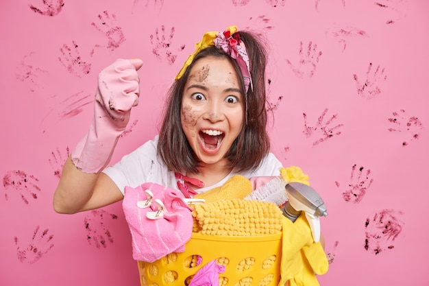 Unordentliche hausfrau ruft laut aus, ballt die faust, macht hausputzposen in der nähe des wäschekorbs hat schmutziges gesicht isoliert über rosa wand Kostenlose Fotos