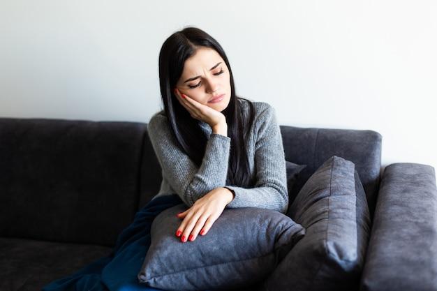 Unpässliche kranke frau spürt ihre temperatur, während sie zu hause auf dem sofa ruht