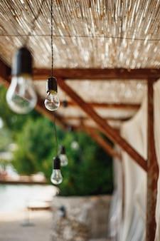 Unpluged girlande aus glühbirnen unter der strohgedeckten decke