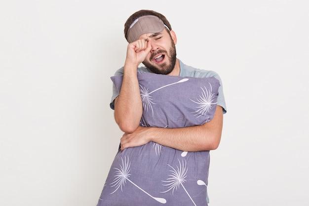 Unrasierter gähnender mann, der drinnen posiert, sich die augen reibt, den mund offen hält, das graue kissen in den händen hält und morgens aufwacht