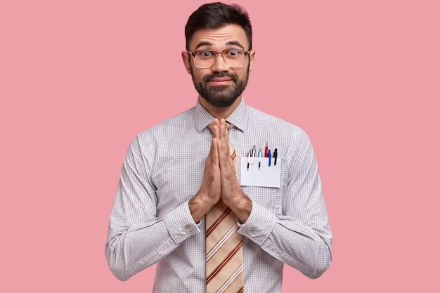 Unrasierter junger europäischer mann mit dicken borsten, bittet um hilfe oder verspricht treue, hält die handflächen zusammengedrückt, trägt eine quadratische brille