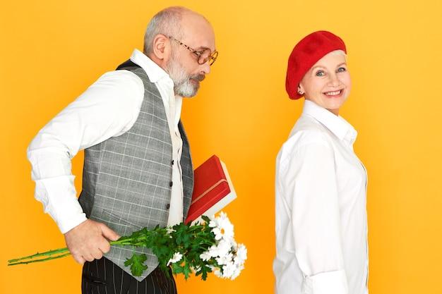 Unrasierter kahler älterer mann, der elegante kleidung trägt, die bündel gänseblümchen und bof schokolade hält und geburtstagsgeschenk zu seiner charmanten frau macht. konzept für menschen, alter, ehe und beziehungen