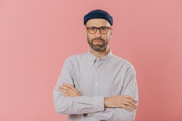 Unrasierter mann kreuzt hände über kasten, trägt die schauspiele und weißes hemd, getrennt über rosafarbenem hintergrund