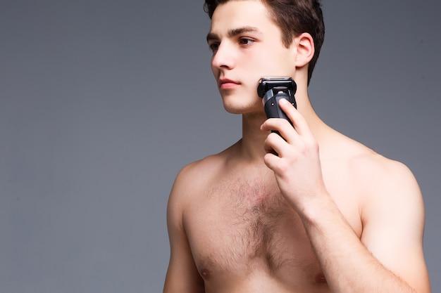 Unrasierter mann mit nacktem oberkörper freut sich auf und verwendet trimmer
