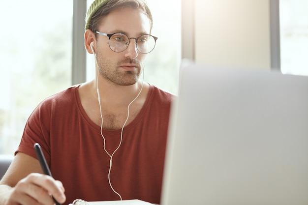 Unrasierter modischer gutaussehender mann mit ansprechenden augen trägt runde brillen