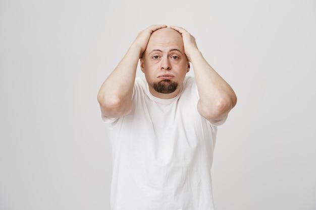 Unruhiger glatzkopf atmet aus und greift nach dem kopf, sieh besorgt aus