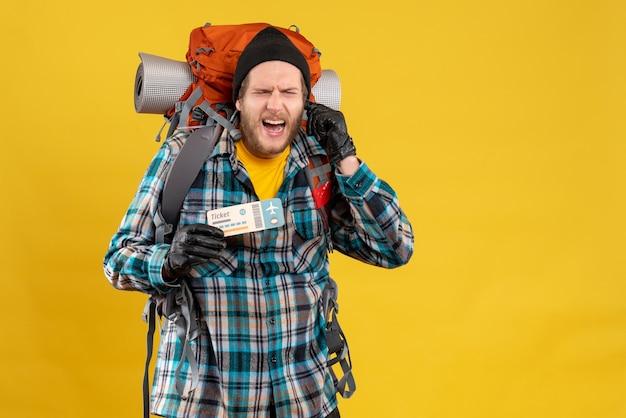 Unruhiger junger rucksacktourist mit schwarzem hut, der flugticket und ohr hält
