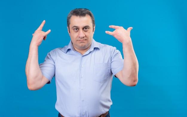 Unruhiger mann mittleren alters im blau gestreiften hemd, das hände im felsensymbol auf blauem hintergrund hält