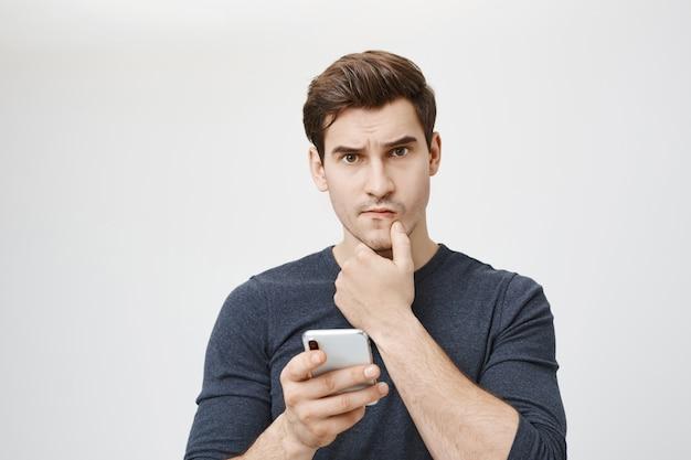 Unruhiger nachdenklicher mann, der denkt, während er smartphone hält