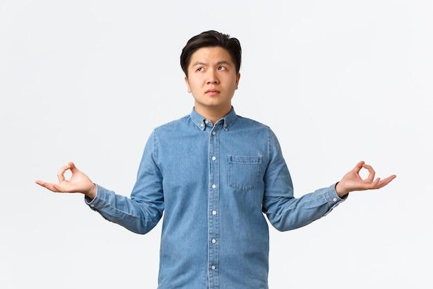 Unruhiger und besorgter asiatischer mann, der nachdenklich wegschaut, überlegt, wie er versucht, zu meditieren und sich zu beruhigen, die hände seitlich in zen-geste ausbreitet, yoga macht, sich nicht konzentrieren kann, weißer hintergrund