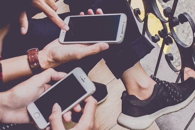 Unschärfe, abschluss oben von den mannhänden, die rührenden handy mit leerem kopienraum für ihre textnachricht im café, weinleseton halten selektiver fokus