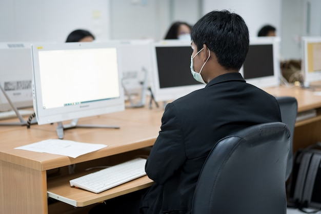 Unschärfe und selektiver fokus der erwachsenen universitätsstudenten, die eine gesichtsmaske tragen, während sie sich auf die online-prüfung im computerraum konzentrieren. ernsthafte studenten, die an der universität am computer arbeiten