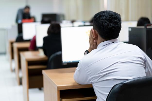 Unschärfe und selektiver fokus des universitätsstudenten, der computer im computerraum verwendet. gruppe von studenten, die im computerraum studieren. ernsthafte studenten, die an der universität an computern arbeiten.