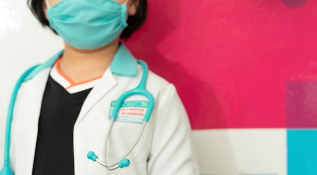 Unschärfefoto des kinderarztes mit stethoskop im weißen kittel auf farbigem hintergrund mit kopierraum