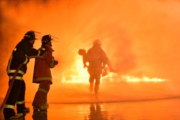Unschärfen und silhouetten von feuerwehrleuten, die brände löschen und opfern helfen.