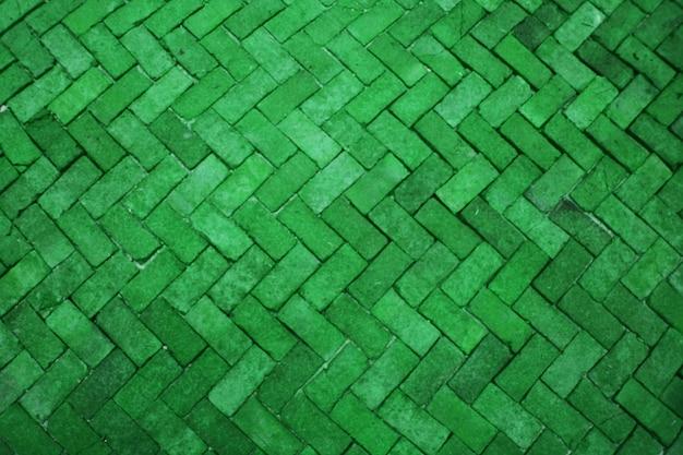 Unscharfe alte grüne moosziegelbodenpflasterstein-luxuswand