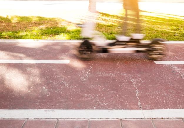 Unscharfe bewegung einer person, die einen roller in einem stadtpark reitet