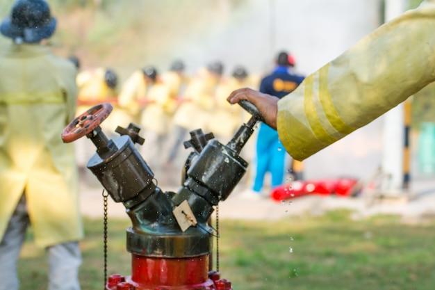 Unscharfe feuerwehrmänner, die wasser vom schlauch für die brandbekämpfung verwenden