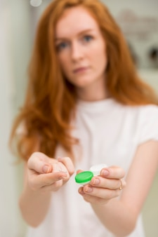 Unscharfe frau, die kontaktlinse mit ihr zeigt, ist behälter