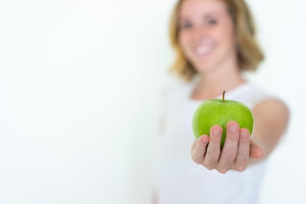 Unscharfe frau, die reifen grünen apfel anbietet