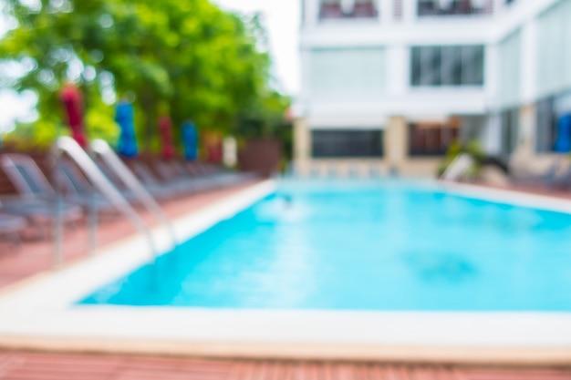Unscharfe hängematten mit bunten sonnenschirmen in einem pool