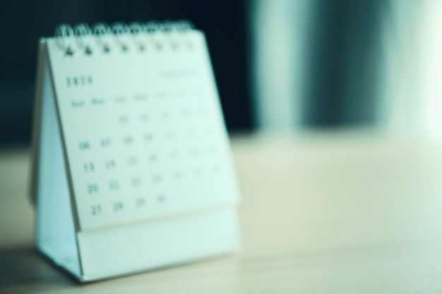 Unscharfe kalenderseite schließen oben auf holztabellenhintergrund-geschäftsplanungs-termin-besprechungskonzept