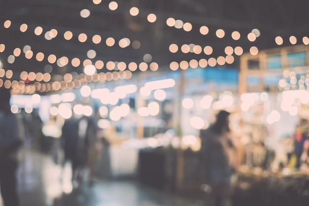 Unscharfe nachtmarktfestivalleute, die auf straße gehen