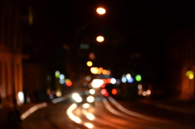 Unscharfe nachtszene des verkehrs auf der fahrbahn. defokussiertes bild von autos, die mit leuchtenden scheinwerfern reisen.