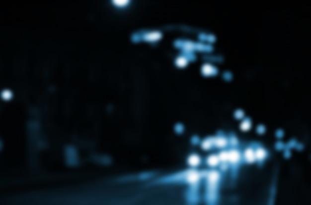 Unscharfe nachtszene des verkehrs auf der fahrbahn. unscharf gestelltes bild von autos, die mit leuchtenden scheinwerfern reisen. bokeh art