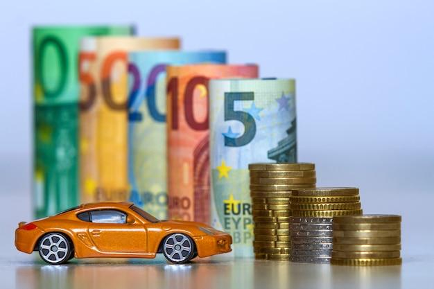 Unscharfe reihe von gerollten eurobanknoten und von stapel von münzen mit gelbem spielzeugsportwagen